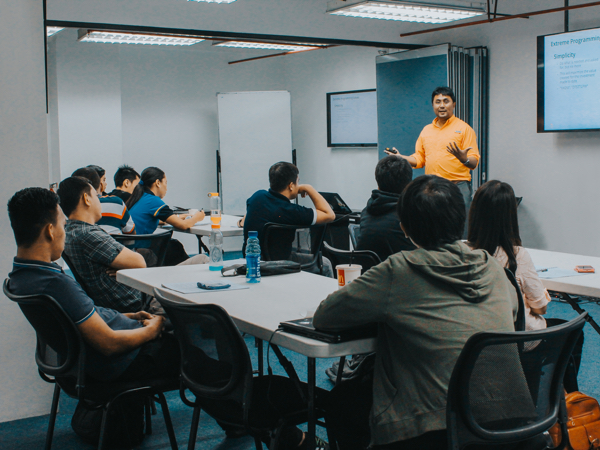Calen Legaspi with his students equipping them with the right skills to deliver quality software application | Orange & Bronze