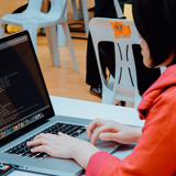 A student in front of her laptop that shows her code. | Java Training Track | Orange and Bronze Software Labs